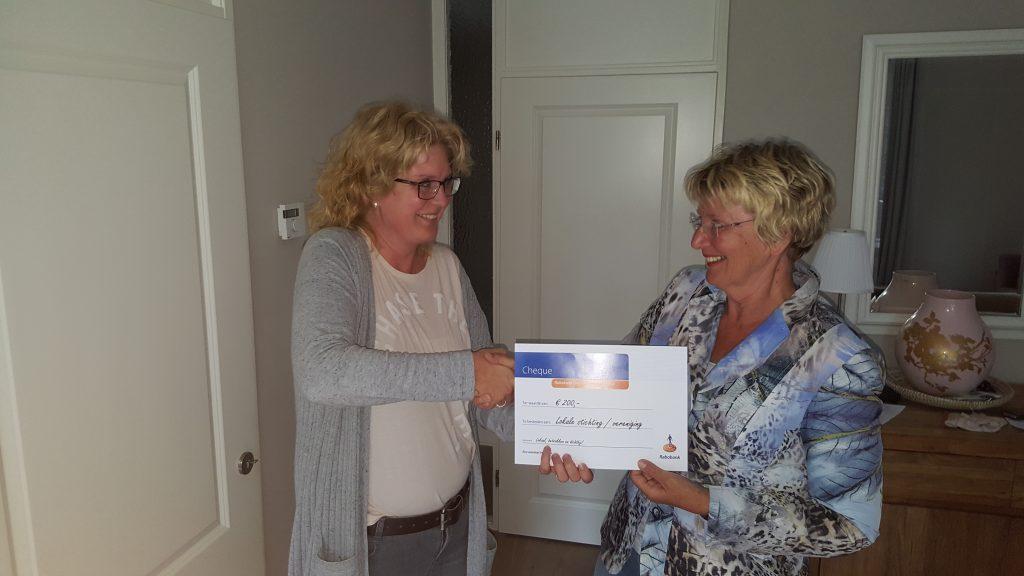 Annet van der Molen overhandigt de cheque aan Geke van Boekel.